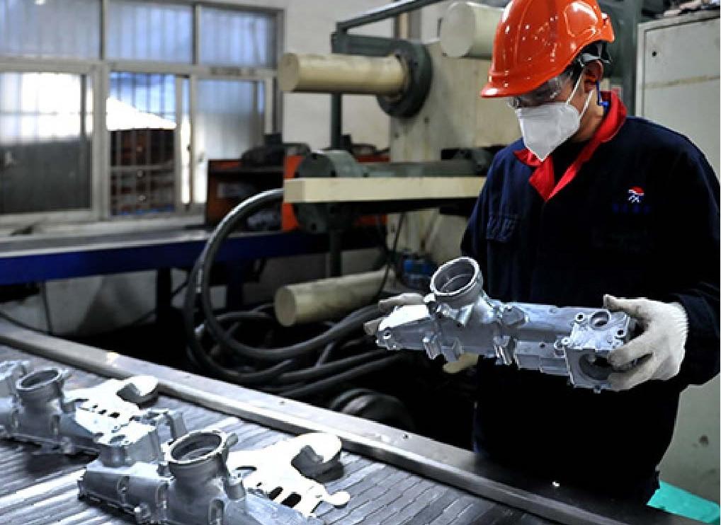 Staff checking CNC precision machined parts quality